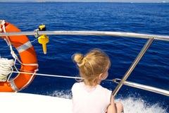 Blondes Segeln der hinteren Ansicht des kleinen Mädchens im Boot Stockfotos