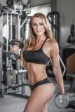 Blondes sexy Bodybuildertraining mit Dummköpfen Lizenzfreies Stockfoto
