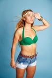 Blondes sexy Mädchen mit kurzen Jeans auf Blau Stockfotografie