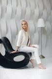 Blondes sexy schönes Mädchen mit dem langen Haar- und Zaubermake-up, das im Studio aufwirft Stockbild