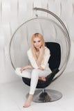 Blondes sexy schönes Mädchen mit dem langen Haar- und Zaubermake-up, das im Studio aufwirft Stockbilder