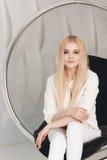 Blondes sexy schönes Mädchen mit dem langen Haar- und Zaubermake-up, das im Studio aufwirft Stockfoto