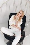Blondes sexy schönes Mädchen mit dem langen Haar- und Zaubermake-up, das im Studio aufwirft Lizenzfreies Stockfoto