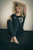 Blondes Sitzen auf dem Boden Stockfoto