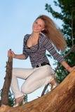 Blondes Sitzen auf einem Baumzweig Lizenzfreies Stockbild