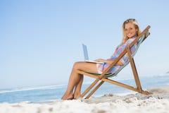 Blondes Sitzen auf Strand unter Verwendung ihres Laptops, der an der Kamera lächelt Stockbild