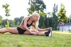 Blondes sportliches Frauenausdehnen im Freien Stockfoto