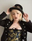 Blondes Steampunk-Mädchen im Hut und Schutzbrillen, die überrascht schauen Stockfotografie