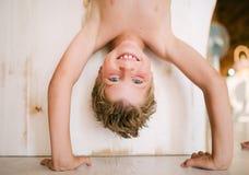 Blondes stehendes umgedrehtes des Jungen auf seinen Händen Stockbild