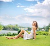 Blondes Stillstehen auf dem frischen grünen Rasen Lizenzfreies Stockfoto