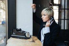 Blondes stilvolles Mädchen, das altmodisches Telefon verwendet Stockbild