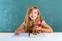 Blondes Studentenmädchen mit Hündchen am Klassenbrett Stockbilder