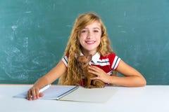 Blondes Studentenmädchen mit Hündchen am Klassenbrett Lizenzfreies Stockfoto