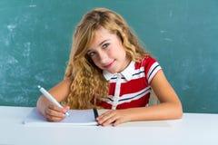 Blondes Studentenmädchen-Schreibensnotizbuch am Klassenschreibtisch Lizenzfreie Stockfotografie