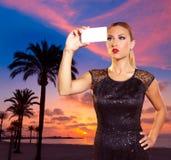 Blondes touristisches Mädchen, das Fotos von Mallorca-Sonnenuntergang macht Stockfotos