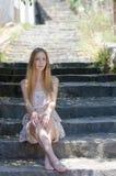 Blondes tragendes Blumenkleid der Mode, das auf Steintreppe sitzt Stockbild