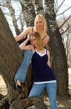 Blondes and trees. Two cute blondes amongst some trees at a park Stock Photos