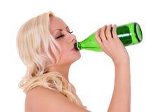 Blondes trinkendes Bier der jungen Frau von der grünen Glasflasche Lizenzfreies Stockfoto