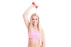 Blondes und überzeugtes Eignungsmädchen, das mit hellen Gewichten trainiert Stockbilder