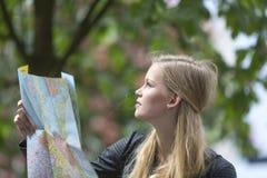 Blondes und junges Mädchen, das auf einer Karte schaut Stockbild