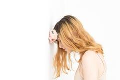 Blondes unten schauen der Junge recht mit ihrem Arm auf der Wand und dem hea Lizenzfreie Stockfotografie