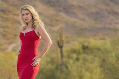 Blondes vorbildliches In ein rotes Kleid, das draußen aufwirft Lizenzfreie Stockfotos