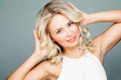 Blondes vorbildliches Girl mit gesunder Haut und dem gelockten Haar Stockbild