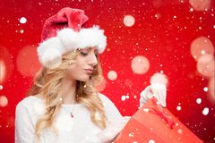 Blondes vorbildliches Girl in Santa Hat über Rot Lizenzfreie Stockfotos
