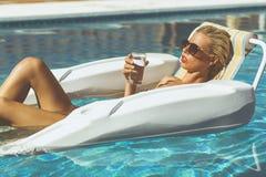 Blondes vorbildliches Kühlen in einem Pool Stockfotografie