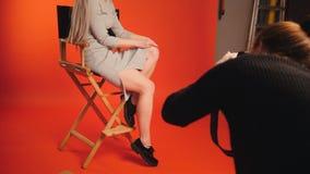 Blondes vorbildliches Mädchen im Fotostudio, das auf Stuhl sitzt - arbeiten Sie Bühne hinter dem Vorhang um Lizenzfreies Stockfoto