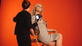 Blondes vorbildliches Mädchen im Fotostudio - Fotograf richtet Haar, Modebühne hinter dem vorhang gerade Lizenzfreie Stockbilder