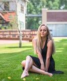 Blondes vorbildliches Sitzen auf dem Gras Lizenzfreie Stockfotos