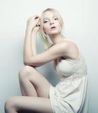 blondes vorbildliches Sitzen auf einem Schemel Lizenzfreie Stockfotos
