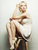 blondes vorbildliches Sitzen auf einem Schemel Stockfotografie