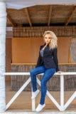 Blondes vorbildliches Sitzen auf weißem Zaun Lizenzfreies Stockbild