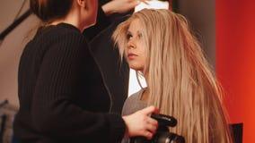 Blondes weißes kaukasisches vorbildliches Mädchen im Fotostudio - Fotograf richtet Haar, Modebühne hinter dem vorhang gerade Lizenzfreies Stockbild