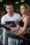 Blondes weibliches Ausarbeiten in der Turnhalle mit Trainer Stockfoto