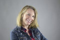 Blondes weibliches Gewinn Blau Jean Jacket Stockfoto