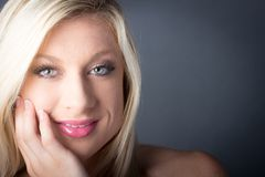 Blondes weibliches haltenes Gesicht in ihrer Hand Lizenzfreies Stockfoto