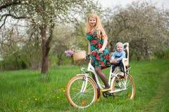 Blondes weibliches Reitstadtfahrrad mit Baby im Fahrradstuhl Stockbilder