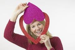 Blondes weibliches Schauen durch Valentinsgruß-Tagesherzen Stockfotografie