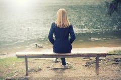 Blondes weibliches Sitzen auf Bank Lizenzfreies Stockbild