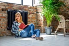 Blondes weibliches Sitzen auf dem Boden und der Lesung ein Buch Stockfotos