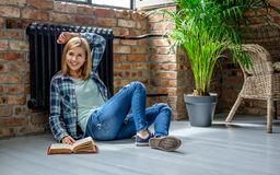 Blondes weibliches Sitzen auf dem Boden und der Lesung ein Buch Stockbilder