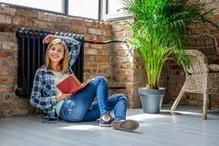 Blondes weibliches Sitzen auf dem Boden und der Lesung ein Buch Lizenzfreies Stockbild