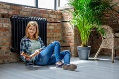 Blondes weibliches Sitzen auf dem Boden und der Lesung ein Buch Stockfoto