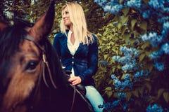 Blondes weibliches Sitzen auf Pferderückseite Lizenzfreies Stockfoto