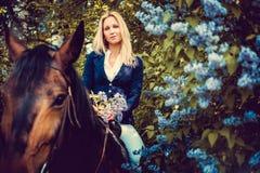 Blondes weibliches Sitzen auf Pferderückseite Lizenzfreie Stockfotografie