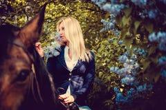 Blondes weibliches Sitzen auf Pferderückseite Lizenzfreie Stockfotos