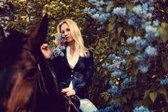 Blondes weibliches Sitzen auf Pferderückseite Lizenzfreie Stockbilder